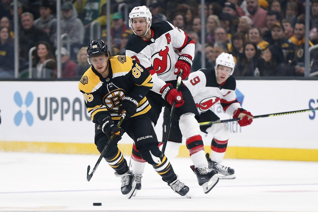 New Jersey Devils' Travis Zajac (19) and Boston Bruins' David Pastrnak (88) battle for the puck during the first period of an NHL hockey game in Bosto