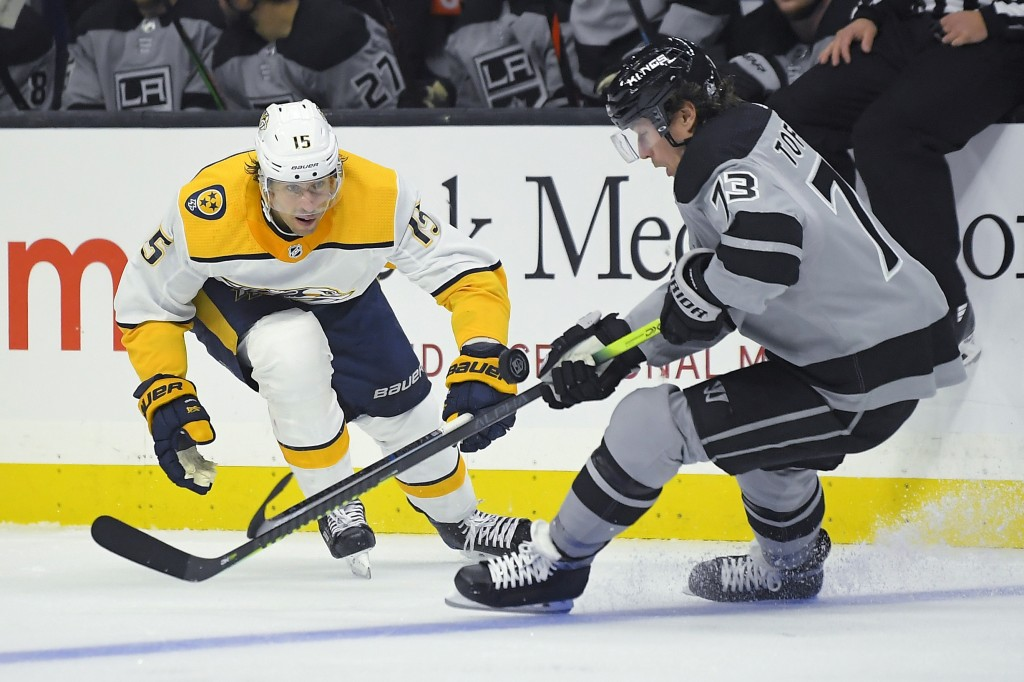 Los Angeles Kings center Tyler Toffoli, right, moves the puck as Nashville Predators center Craig Smith puts pressure on him during the second period ...