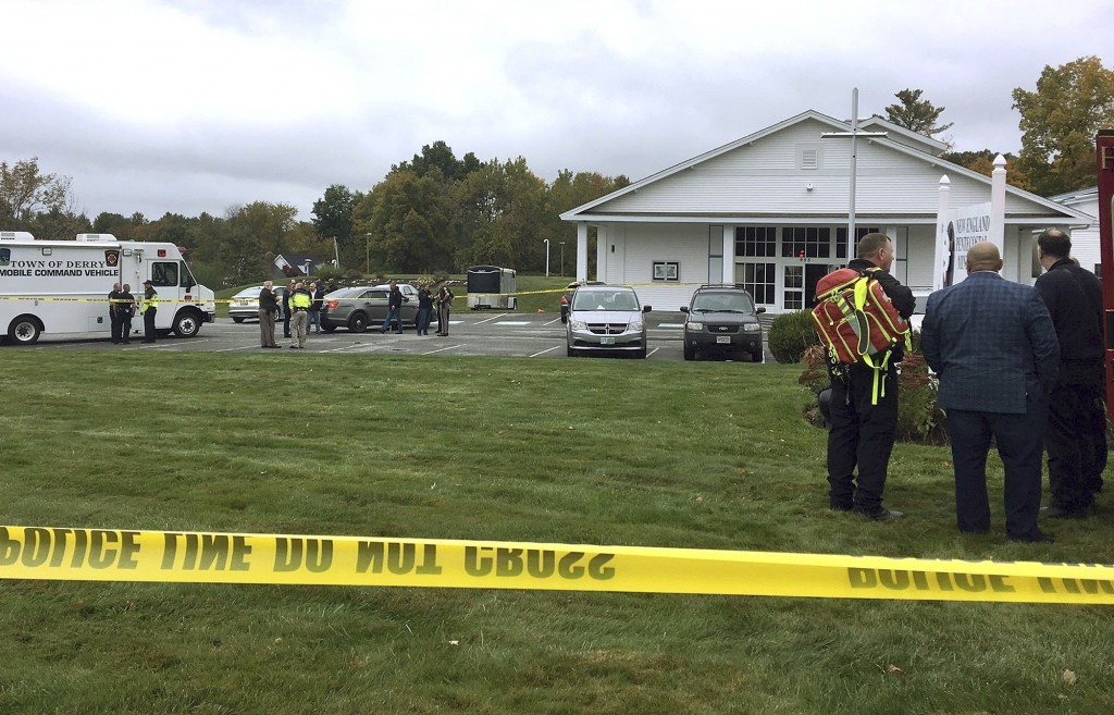 In this photo provided by WMUR-TV, police stand outside the New England Pentecostal Church after reports of a shooting on Saturday, Oct. 12, 2019, in ...