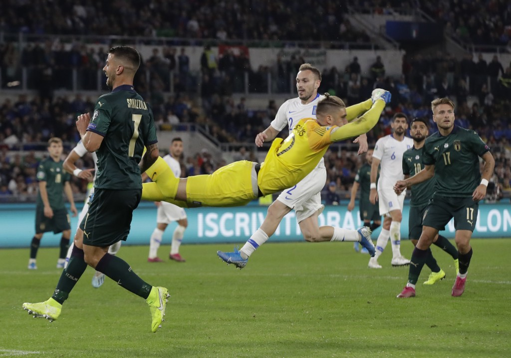 Greece's goalkeeper Alexandros Paschalakis flies through the air after he punches the ball clear as Italy's Lorenzo Pellegrini looks on during the Eur...