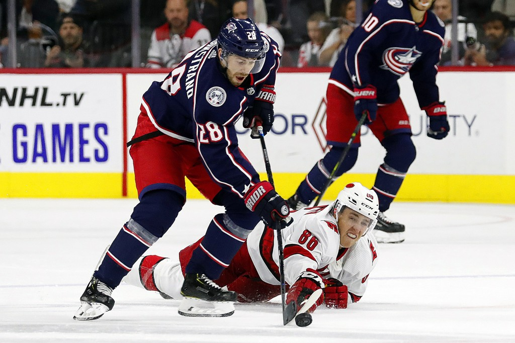 Carolina Hurricanes' Teuvo Teravainen (86), of Finland, dives to poke the puck away from Columbus Blue Jackets' Oliver Bjorkstrand (28), of Denmark, d