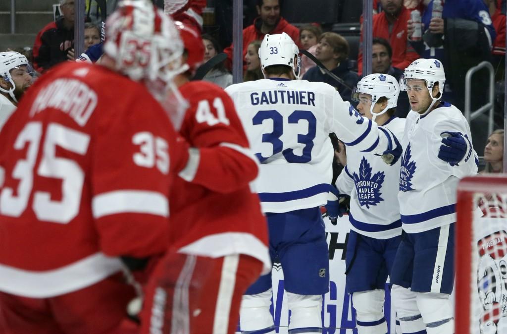 Toronto Maple Leafs center Nicholas Shore, right, celebrates with center Frederik Gauthier (33) and left wing Dmytro Timashov, center, of Ukraine, aft