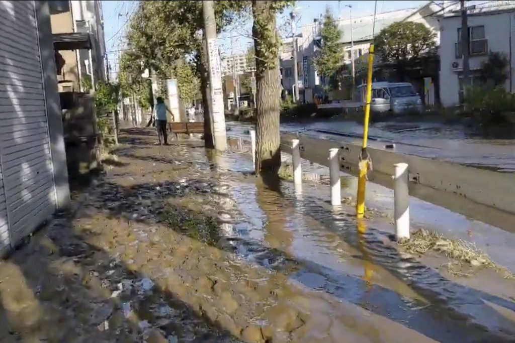 This image made from a video by @ar_kaz shows the mud covered street after the flood water receded on the morning Sunday, Oct. 13, 2019, in Kawasaki, ...