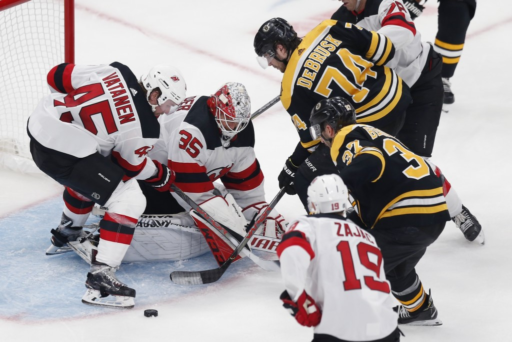 New Jersey Devils' Cory Schneider (35) and Sami Vatanen (45) struggle to gain control of the puck as Boston Bruins' Patrice Bergeron (37) comes in to