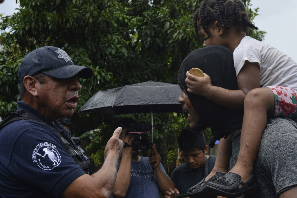 A federal police officer, left, speaks to a migrant carrying a child, right, near Tuzantan, Chiapas state, Mexico, Saturday, Oct. 12, 2019. Hundreds o...