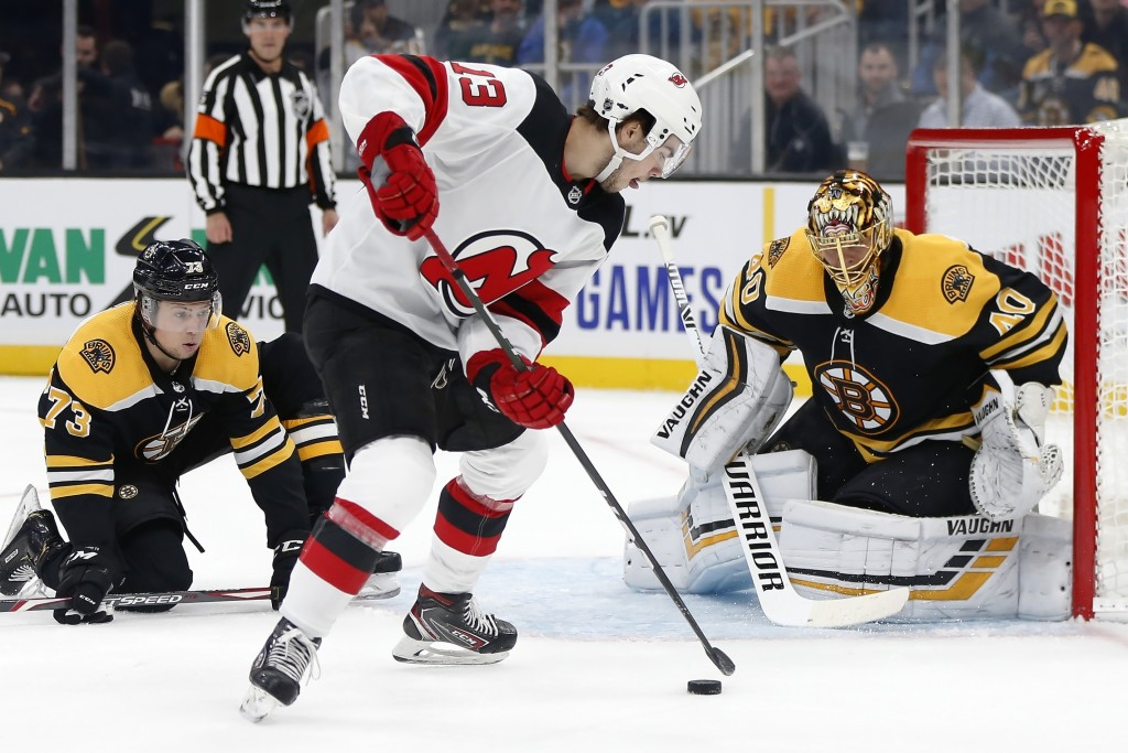 New Jersey Devils' Nico Hischier (13) tries to shoot against Boston Bruins goalie Tuukka Rask (40) during the first period of an NHL hockey game in Bo
