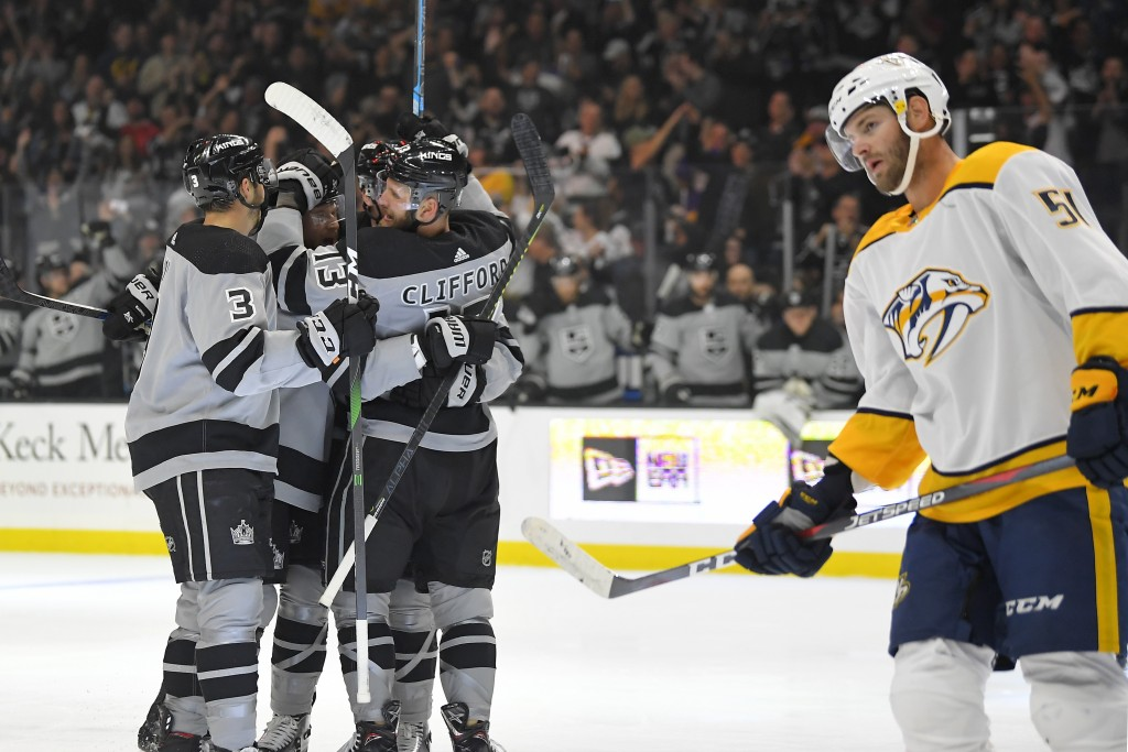 Los Angeles Kings left wing Kyle Clifford, back right, celebrates his goal with defenseman Matt Roy, left, and another teammate, as Nashville Predator...