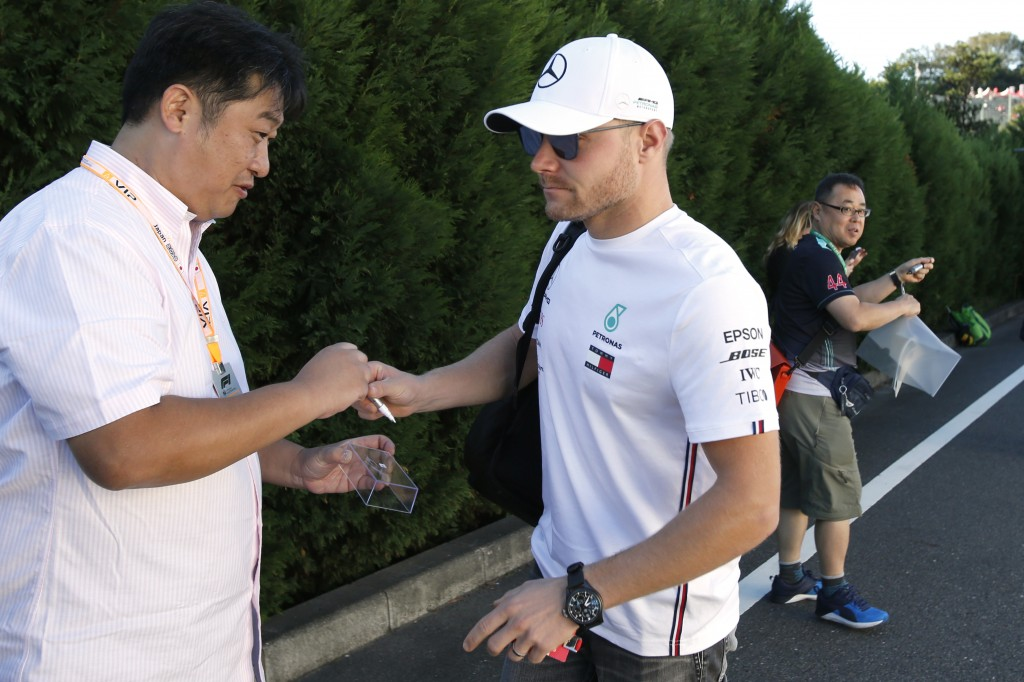 Mercedes driver Valtteri Bottas of Finland returns a pen after signing his autograph to a fan upon arrival at the paddock ahead of the Japanese Formul...