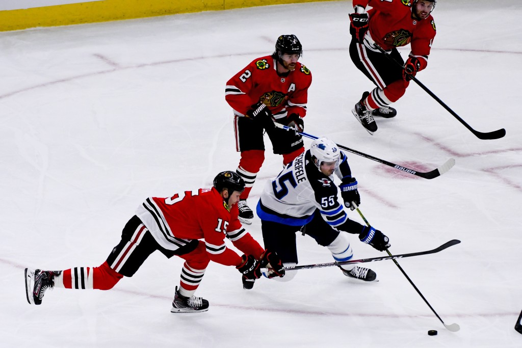 Chicago Blackhawks center Zack Smith (15) and Winnipeg Jets center Mark Scheifele (55) fight for the puck during the third period of an NHL hockey gam...