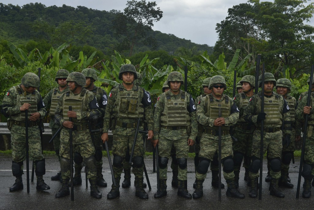 Mexican National Guard members stand with batons during the migrant caravan near Tuzantan, Chiapas state, Mexico, Saturday Oct. 12, 2019. Hundreds of ...