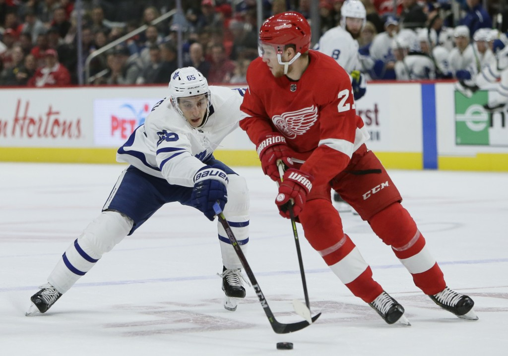 Toronto Maple Leafs right wing Ilya Mikheyev (65), of Russia, tries to steal the puck from Detroit Red Wings defenseman Dennis Cholowski (21), of the ...