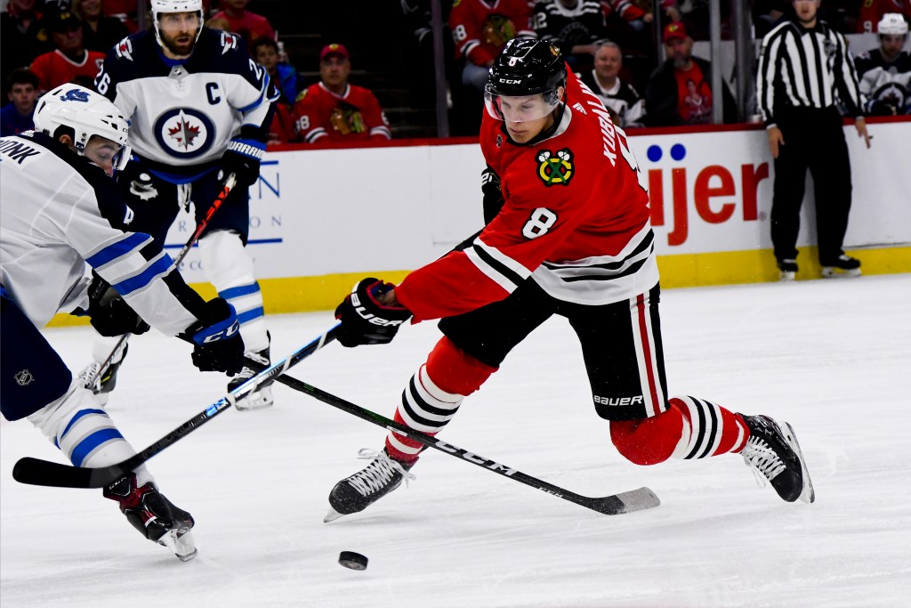 Chicago Blackhawks left wing Dominik Kubalik, right, shoots past Winnipeg Jets defenseman Neal Pionk, left, during the first period of an NHL hockey g