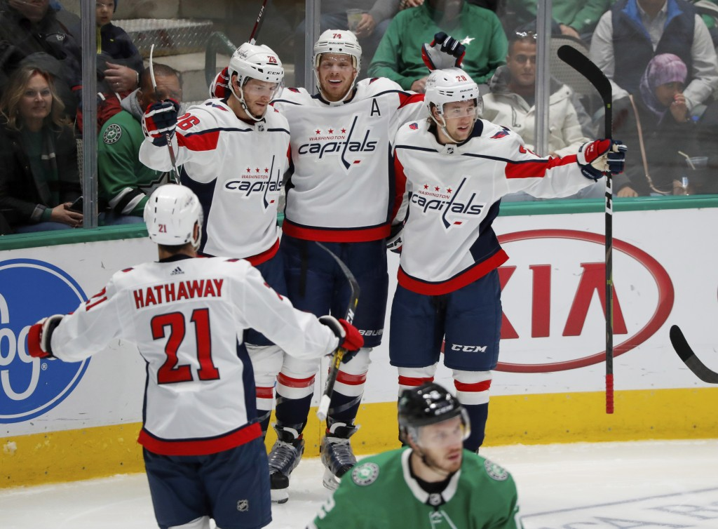 Washington Capitals' Garnet Hathaway (21), Nic Dowd (26), John Carlson (74) and Brendan Leipsic (28) celebrate a goal by Carlson as Dallas Stars defen...