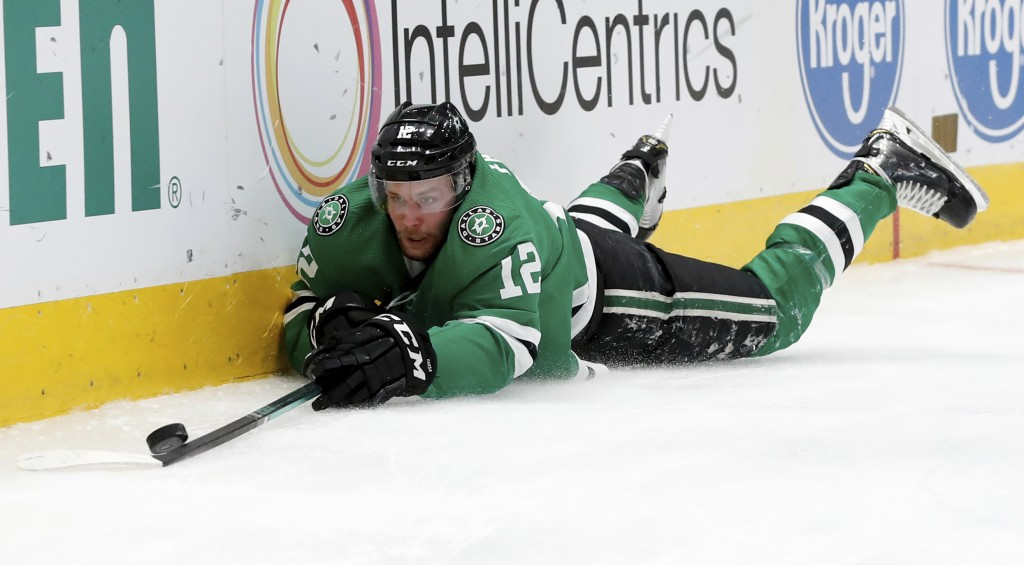 Dallas Stars center Radek Faksa (12) reaches out to control the puck after being tripped in the first period of an NHL hockey game against the Washing