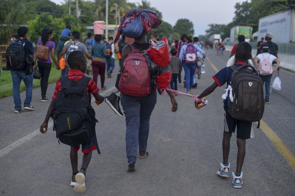 Migrants with bags of belongings walk down the Highway 200 en route to Huixtla near Tapachula, Chiapas, Mexico, Saturday Oct. 12, 2019. Migrants from ...