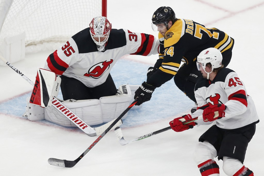 Boston Bruins' Jake DeBrusk (74) tries to shoot against New Jersey Devils' Cory Schneider (35) during the second period of an NHL hockey game in Bosto