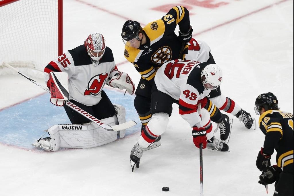 Boston Bruins' Charlie Coyle (13) battles New Jersey Devils' Sami Vatanen (45) in front of Devils goalie Cory Schneider (35) during the second period