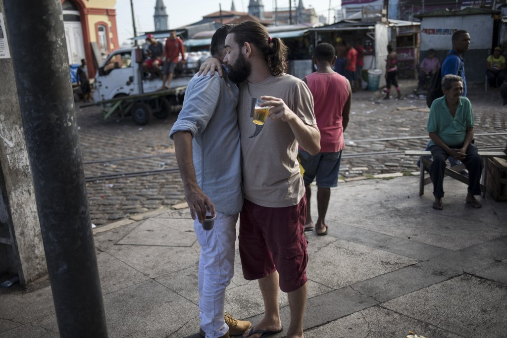 In this Sept. 7, 2019 photo, drunk men embrace early in the morning at the Ver-o-Peso riverside market in Belém, Brazil. Their night probably fueled b...