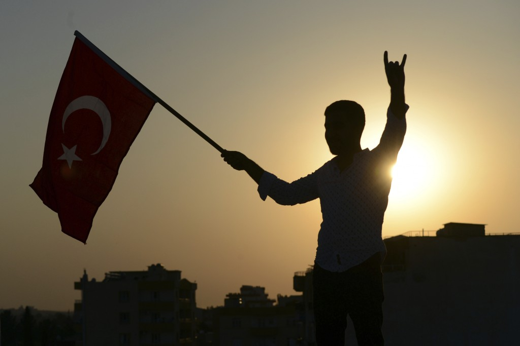 A Turkish youth celebrates with a national flag after news about Syrian town of Tal Abyad, in Turkish border town of Akcakale, in Sanliurfa province, ...