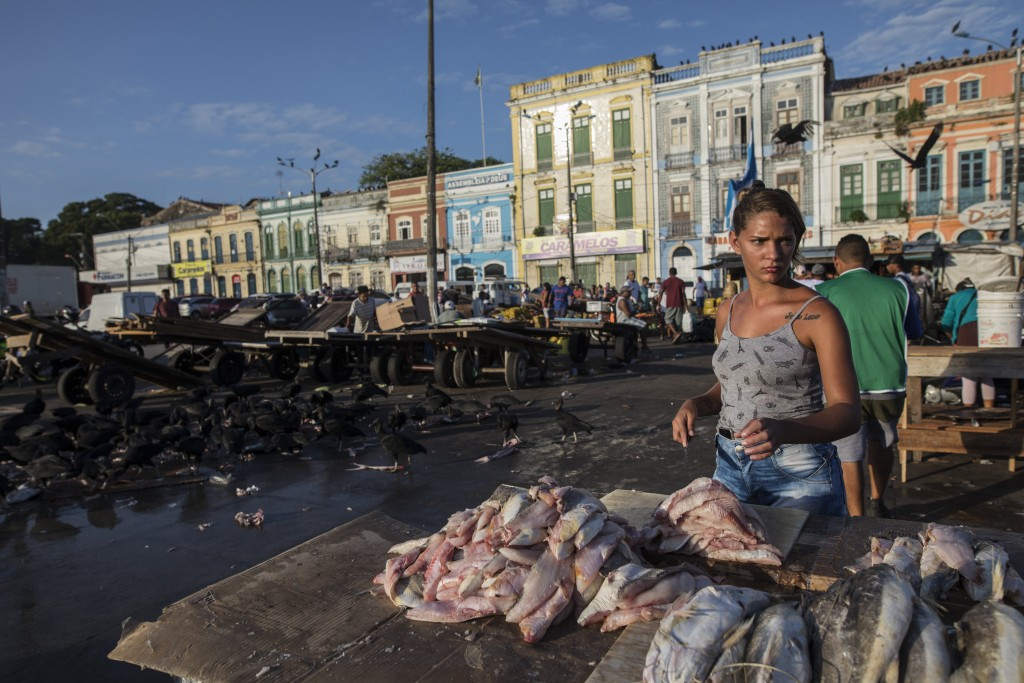 In this Sept. 7, 2019 photo, a fish vendor prepares fish for customers at her street stand at the Ver-o-Peso riverside market in Belém, Brazil. Ver-O-...