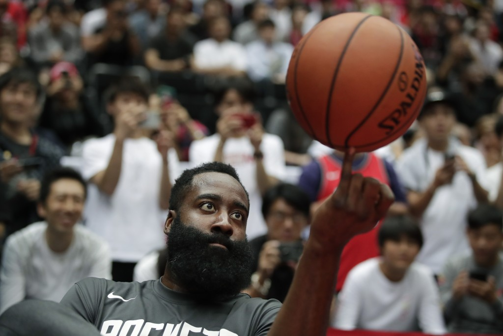 Houston Rockets' James Harden spins the ball during warmups for the team's NBA preseason basketball game against the Toronto Raptors Thursday, Oct. 10...