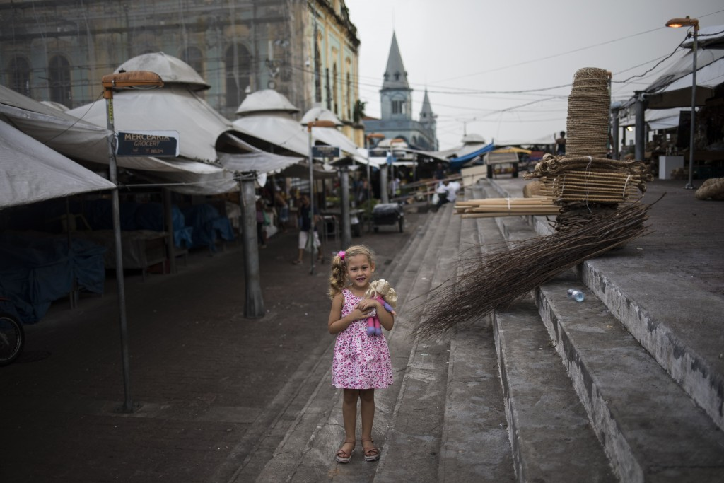 In this Aug. 31, 2019 photo, Valeria, 6, poses for a picture embracing her doll inside the Ver-o-Peso riverside market in Belém, Brazil. The stands at...