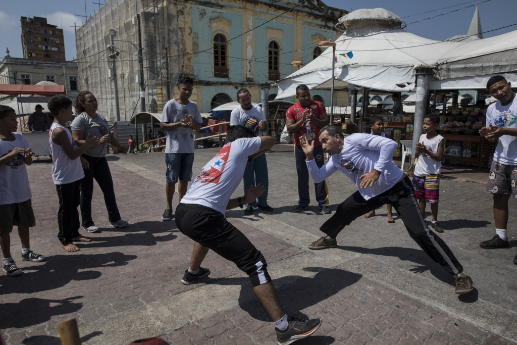In this Sept. 1, 2019 photo, people practice capoeira at the Ver-o-Peso riverside market in Belém, Brazil. Capoeira is an Afro-Brazilian martial art t...