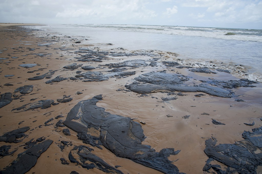 In this Sept. 25, 2019 photo released by the Sergipe state Government, spilt oil lays on the beach on Sergipe state, Brazil. Oil sludge started landin...
