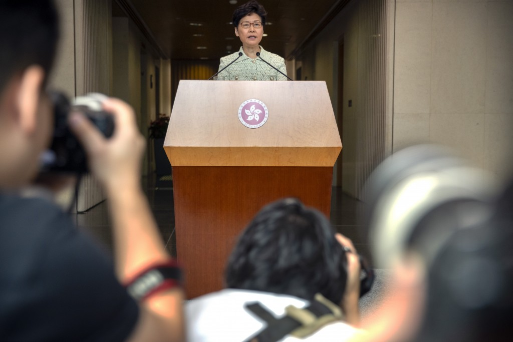 Journalists take photos as Hong Kong Chief Executive Carrie Lam speaks during a press conference at the government building in Hong Kong, Tuesday, Oct...