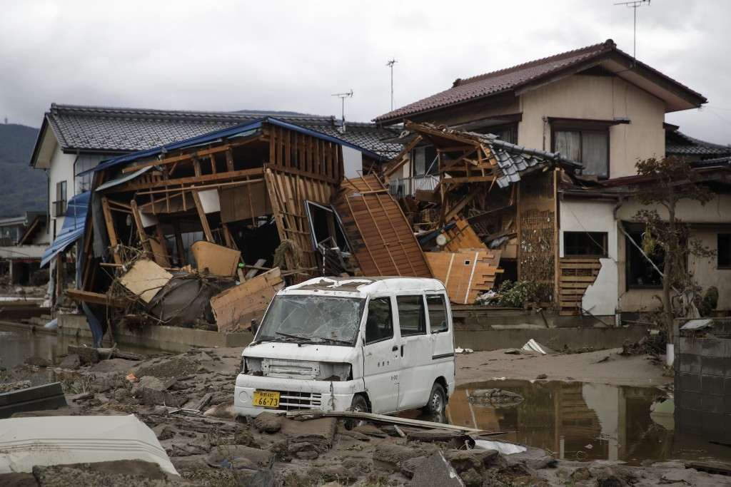 A vehicle sits in front of a home destroyed by Typhoon Hagibis Tuesday, Oct. 15, 2019, in Nagano, Japan. More victims and more damage have been found ...