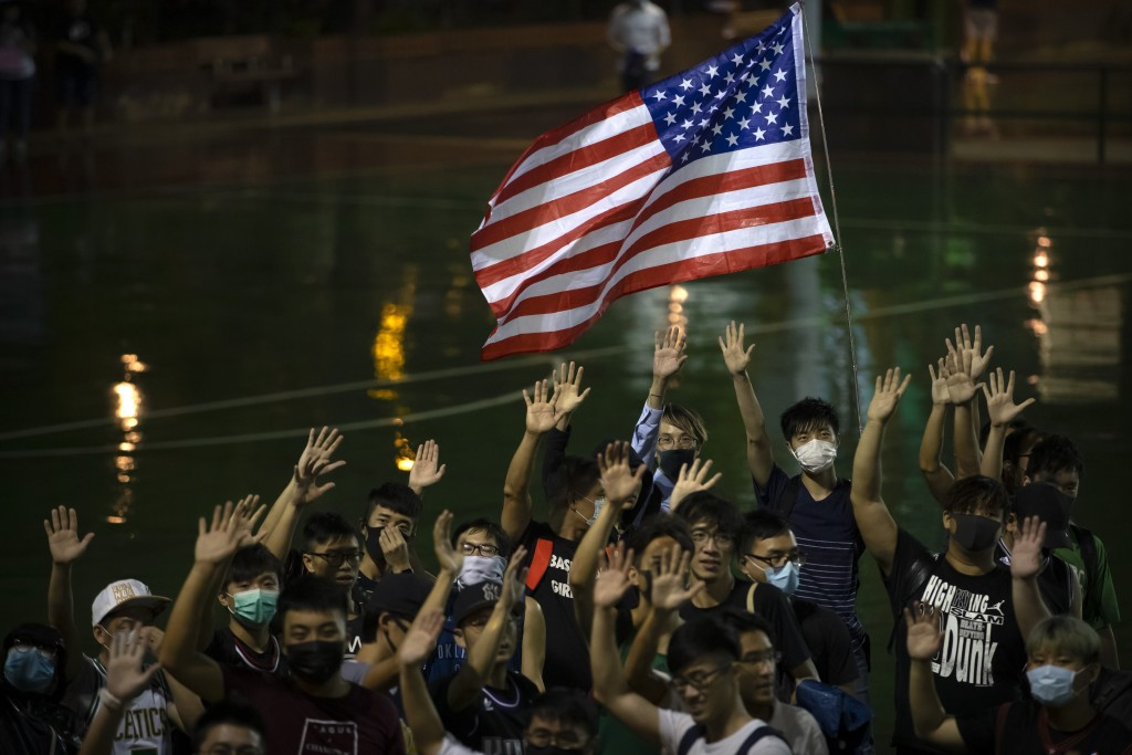 A demonstrator holds a U.S. flag during a rally at the Southorn Playground in Hong Kong, Tuesday, Oct. 15, 2019. Protesters in Hong Kong have thrown b...