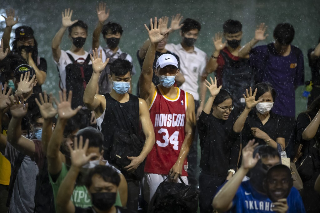 A demonstrator wearing Houston Rockets jersey holds up his hand with fellow demonstrators during a rally at the Southorn Playground in Hong Kong, Tues...