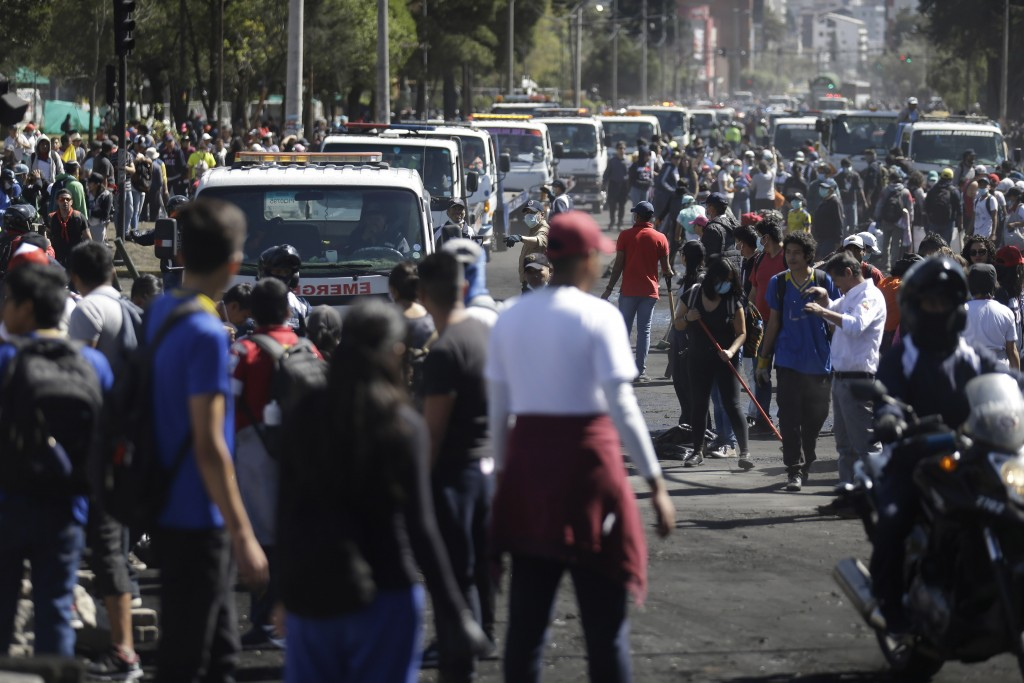 Service trucks line up to remove trash left behind by anti-austerity protesters, in Quito, Ecuador, Monday, Oct. 14, 2019. Thousands of indigenous dem...