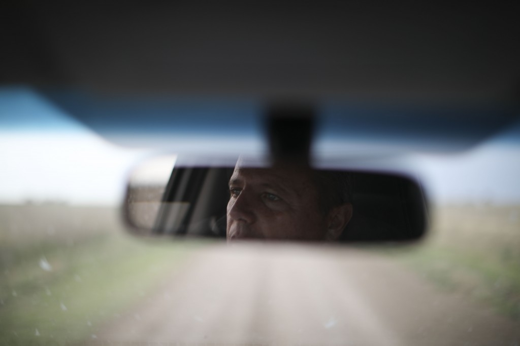 In this Oct. 9, 2019 photo, farmer Juan Rossi is reflected in his rearview mirror on the outskirts of Pergamino, Argentina. Farmers like Rossi are bra...