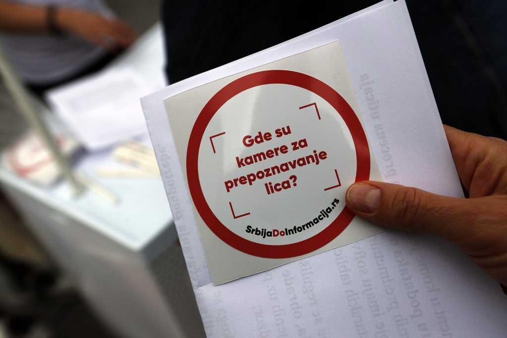 In this photo taken Sept. 25, 2019, an activist in the Serbian capital, Belgrade, shares stickers that read: ''Where are cameras for face recognition?...