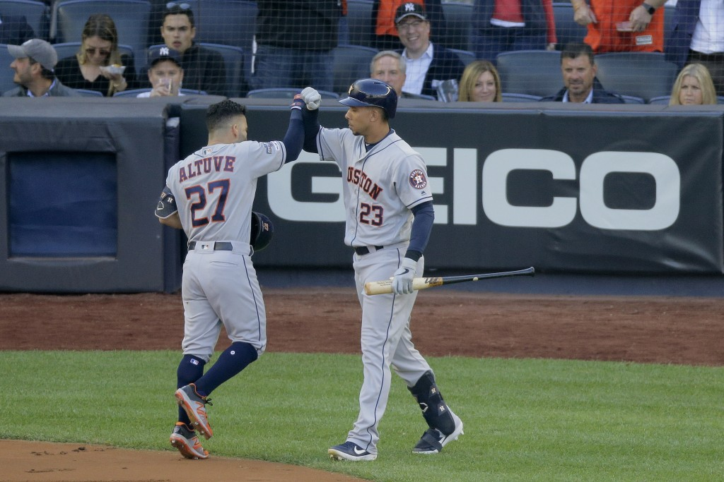 Houston Astros' Jose Altuve (27) is congratulated by Michael Brantley (23) after hitting a solo home run against the New York Yankees during the first...