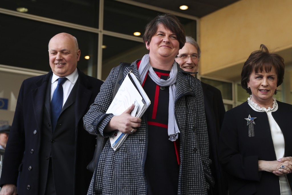 FILE - In this Thursday, April 11, 2019 file photo, Northern Ireland Democratic Unionist Party leader Arlene Foster, center, speaks to journalists aft...