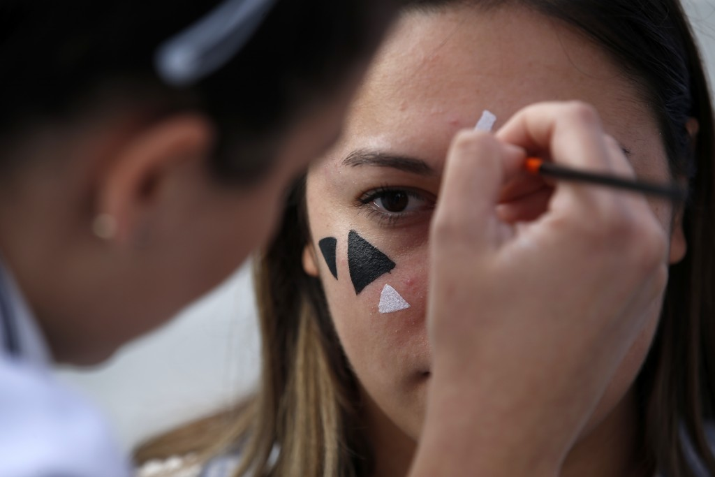 In this photo taken Sept. 25, 2019, members of a rights group paint a face with makeup to confuse the Huawei surveillance video cameras with face-reco...