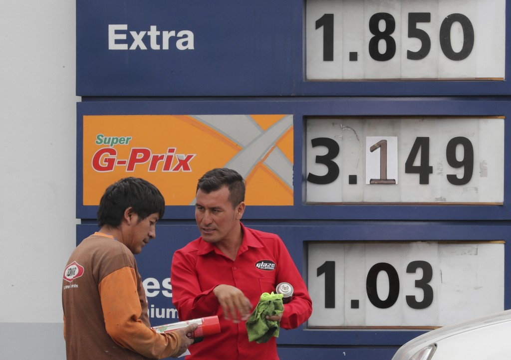 An attendant shows an automotive product to a driver in front of a display with new fuel prices at a gas station in Quito, Ecuador, Tuesday, Oct. 15, ...