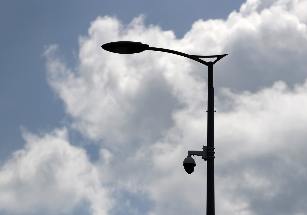 In this photo taken July 17, 2019, a high-tech video camera hangs from a lamppost in Belgrade, Serbia.  A video surveillance system with facial recogn...