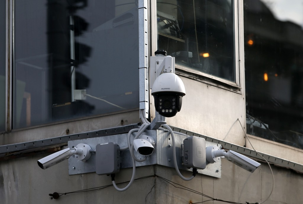 In this photo taken Sept. 25, 2019, high-tech video cameras hang from an office building in downtown Belgrade, Serbia. The cameras, equipped with faci...