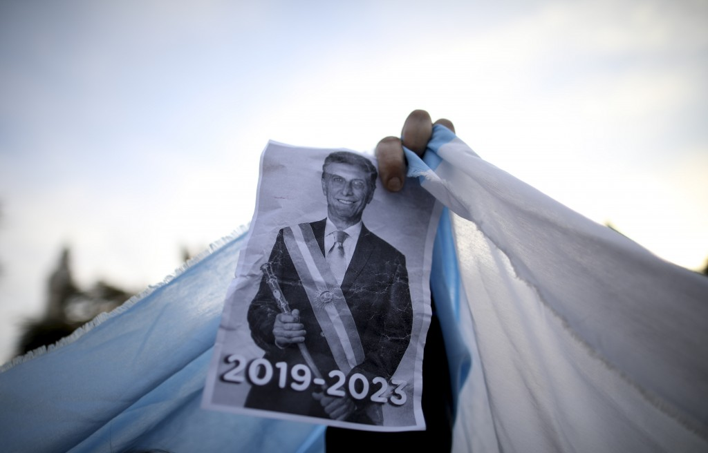 FILE - In this Aug. 24, 2019 file photo, a sopporter holds up an image of President Mauricio Macri during a march in Buenos Aires, Argentina. Many far...