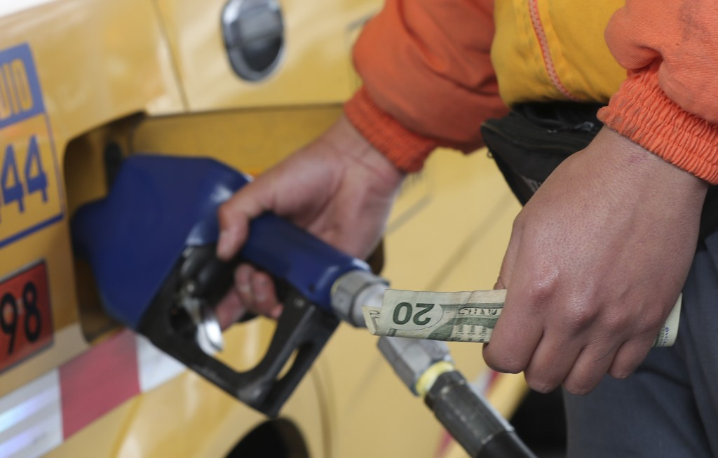 An employee of a gas station fills the fuel tank of a taxi in Quito, Ecuador, Tuesday, Oct. 15, 2019. The recent strike that paralyzed the Andean nati...