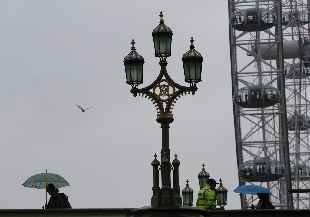 Tourists holding umbrellas pass a policeman standing on Westminster Bridge over the River Thames, with the London Eye in the background as rain falls ...
