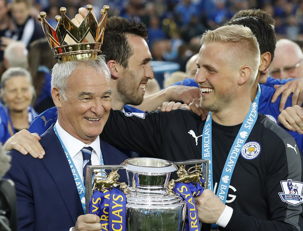 FILE - In this May 7, 2016 file photo, Leicester's team manager Claudio Ranieri gets a crown by Leicester's goalkeeper Kasper Schmeichel as they lift ...