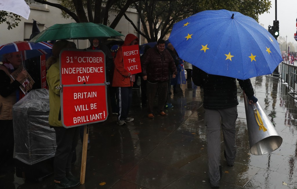Anti-Brexiteer Steve Bray carries his megaphone past pro Brexit supporters as they shelter from the heavy rain outside the Houses of Parliament in Lon...