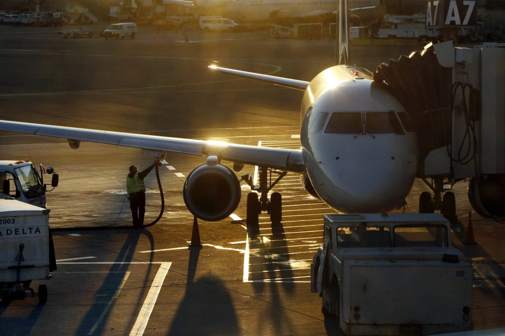FILE - In this Dec. 8, 2018, file photo a worker fuels a Delta Connection regional airlines passenger jet at Logan International Airport in Boston. Mo...