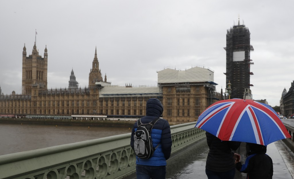 Tourists sheltering underneath a British Union flag umbrella walk across Westminster Bridge in the rain towards the Houses of Parliament in London, Th...