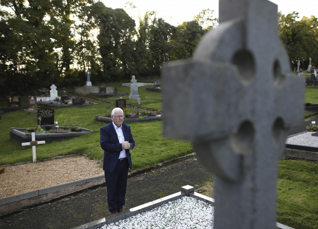 In this photo taken on Wednesday Oct. 16, 2019, Eugene Reavey visits the graves of his three brothers in Whitecross in South Armagh, Northern Ireland.