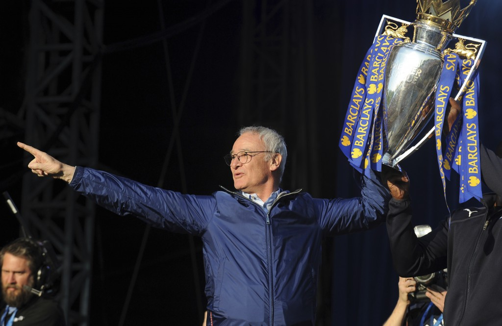 FILE - In this Monday, May 16, 2016 file photo, Leicester's manager Claudio Ranieri shows the Premier League Trophy to fans at Victoria Park during th...
